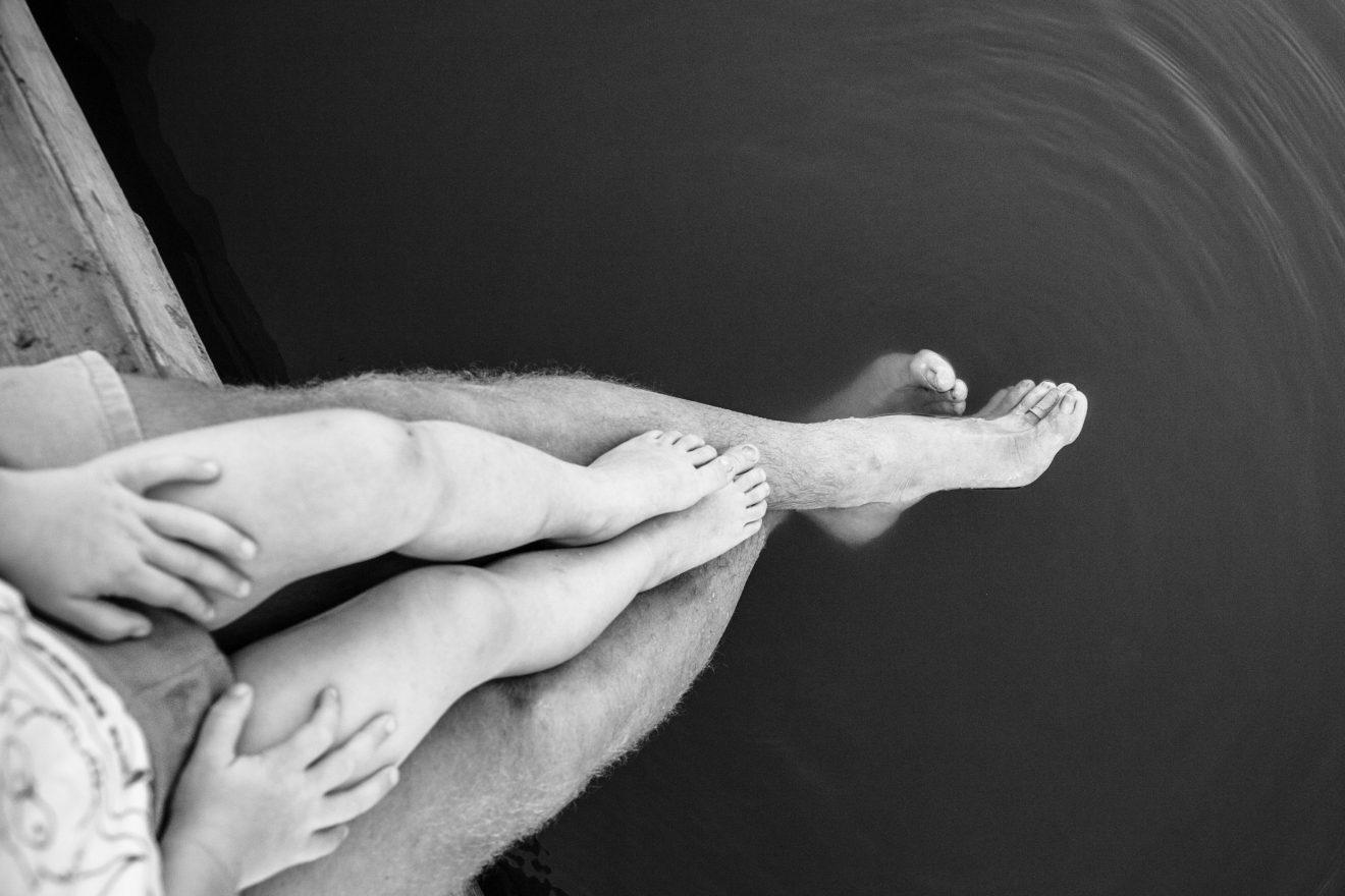 Beine von einem Mann und einem Kind, das auf seinem Schoss sitzt