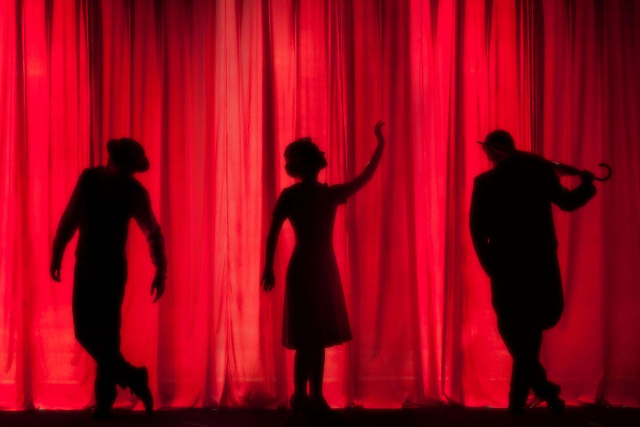 Drei Figuren hinter einem roten Vorhang