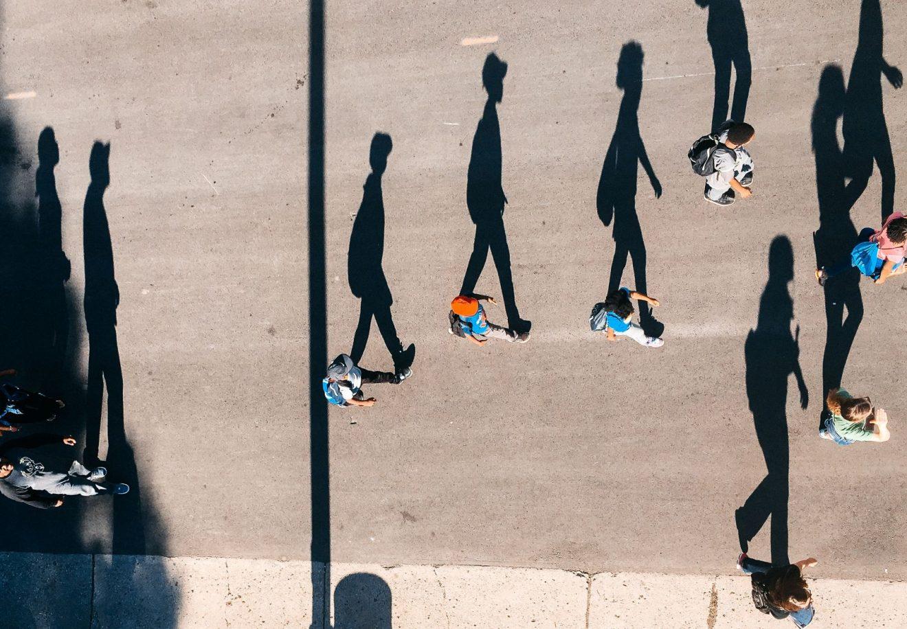 Menschen laufen mit einem großen Schatten